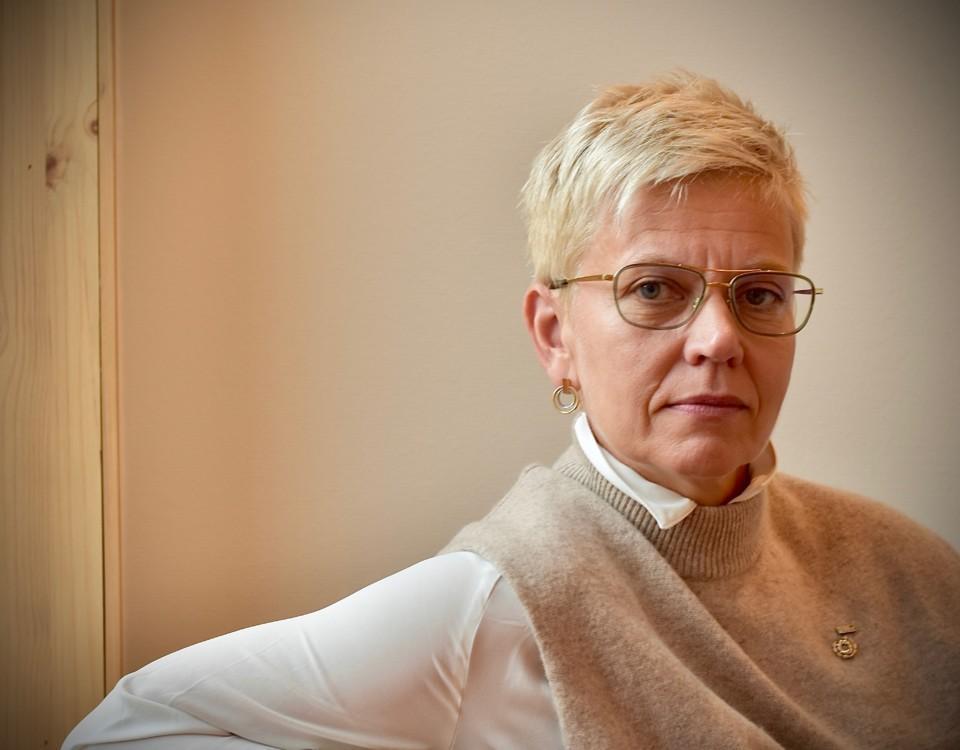 en kvinna med glasögon och stadig blick i kameran