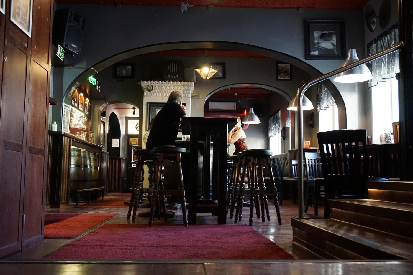 en vy av en pub med ett par människor som sitter på höga barstolar vid bord