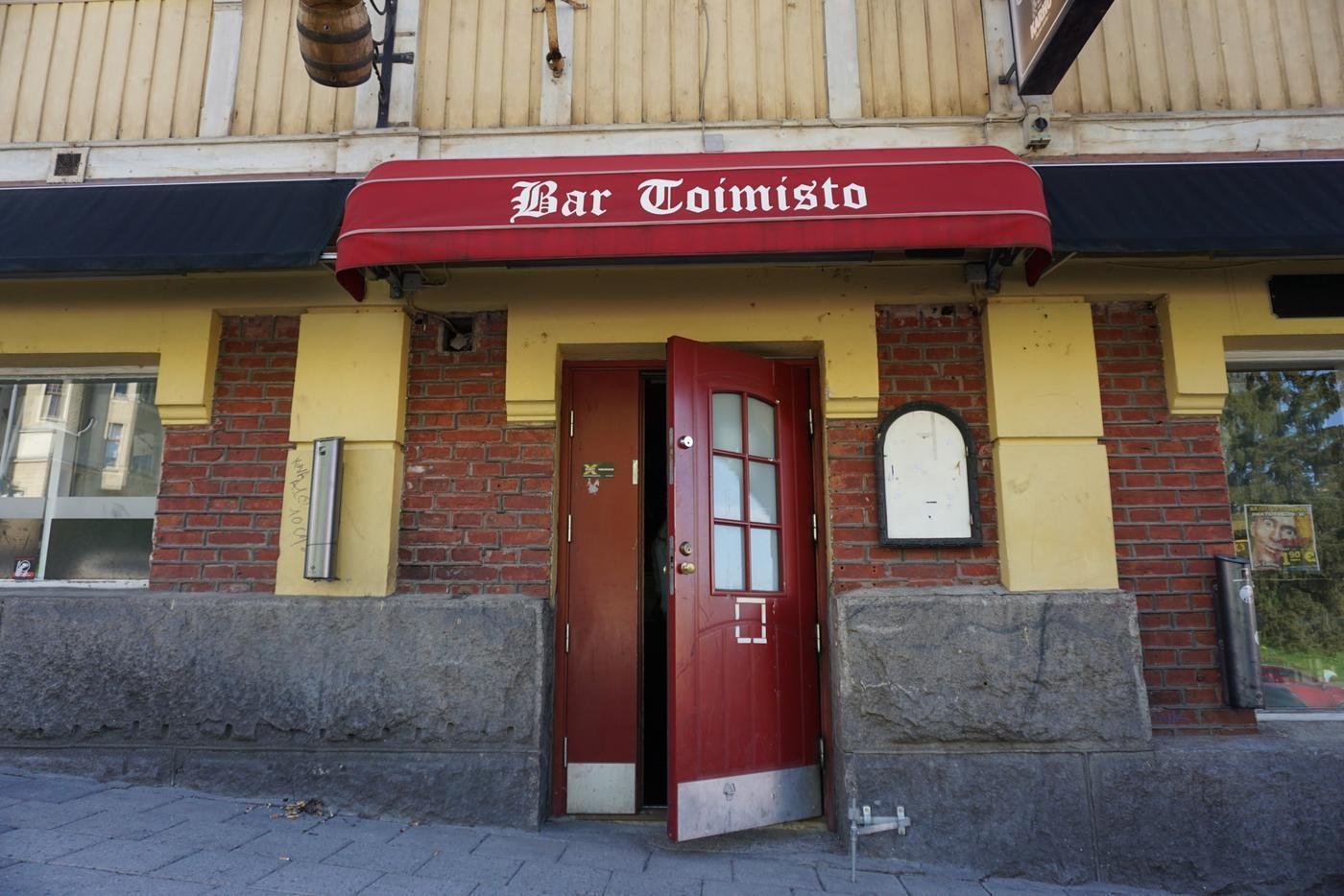 """en röd dörr till står på glänt, ovanför står texten """"Bar Toimisto"""""""