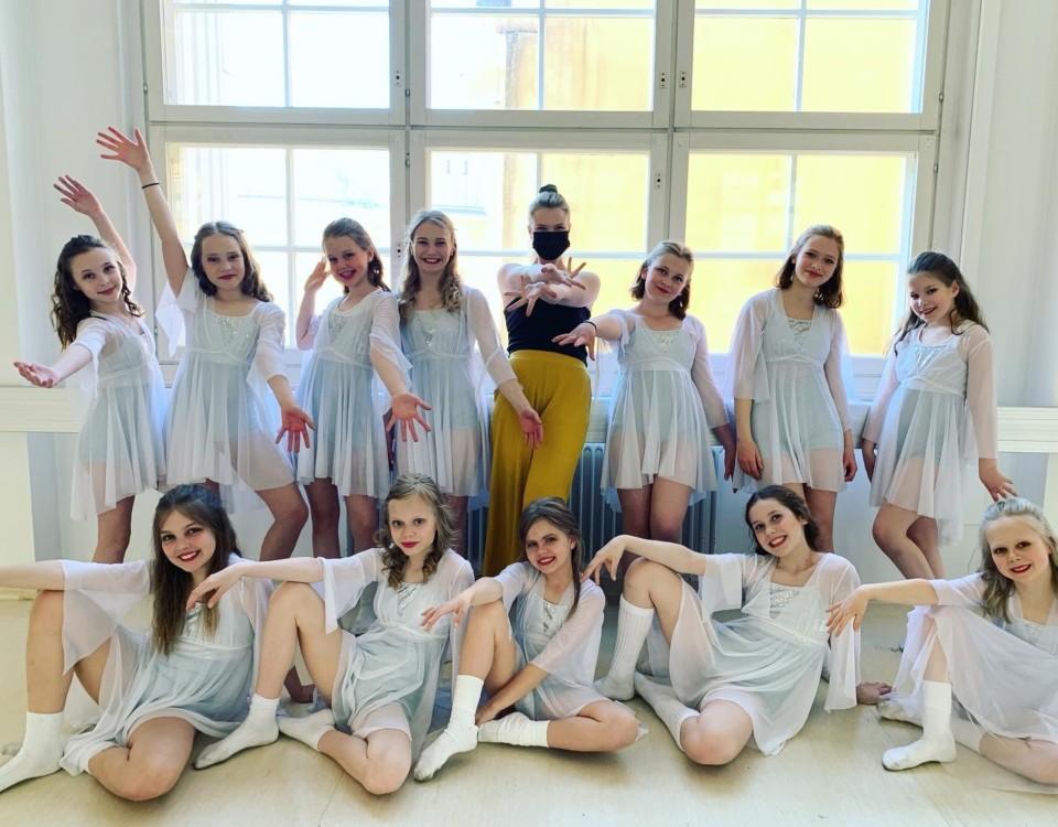 En grupp med dansare poserar framför kameran.