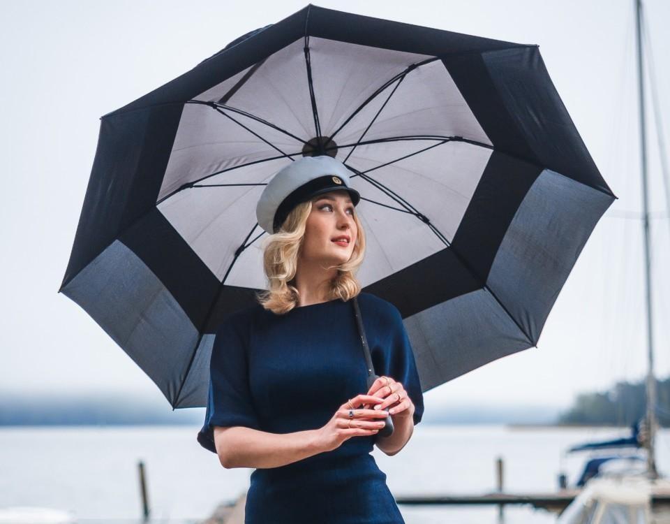 En ung kvinna iklädd studentmössa och klänning står ute på en brygga med ett paraply över huvudet.