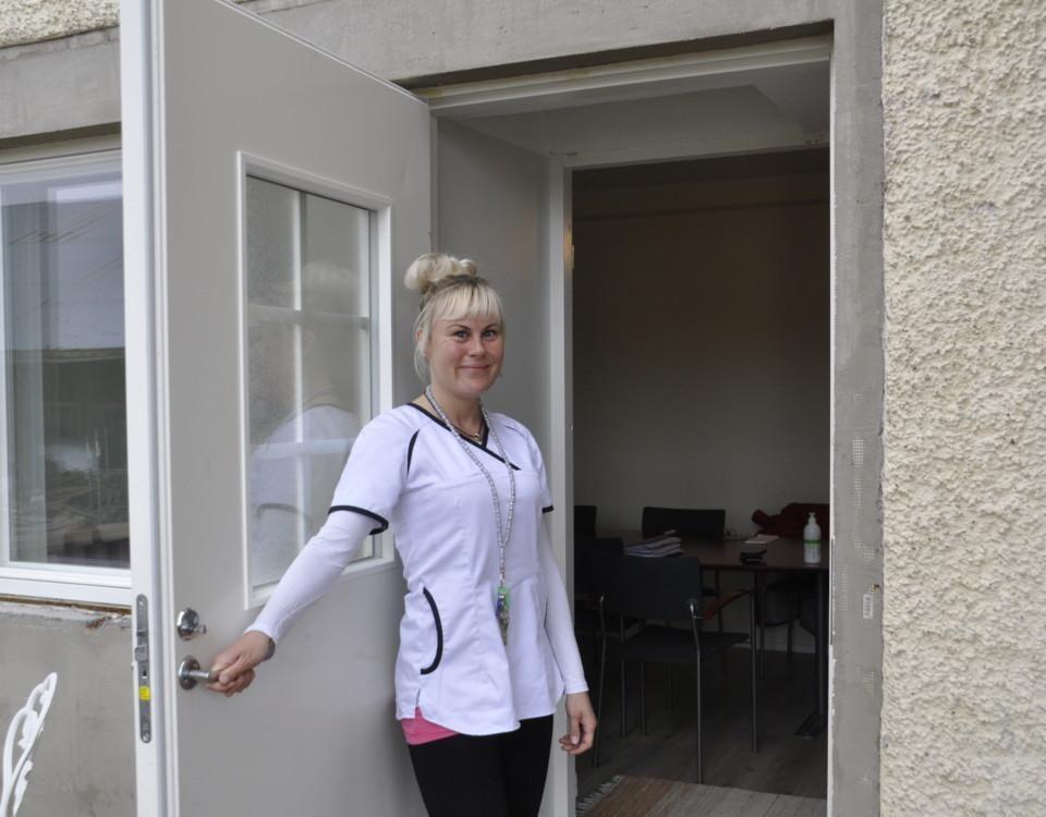 Sjukskötare öppnar dörren till ett mottagningsrum