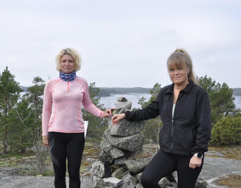 Två damer i gympakläder på ett berg