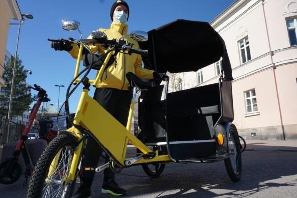 en gul cykelriksha och en gulklädd chaufför som står vid den