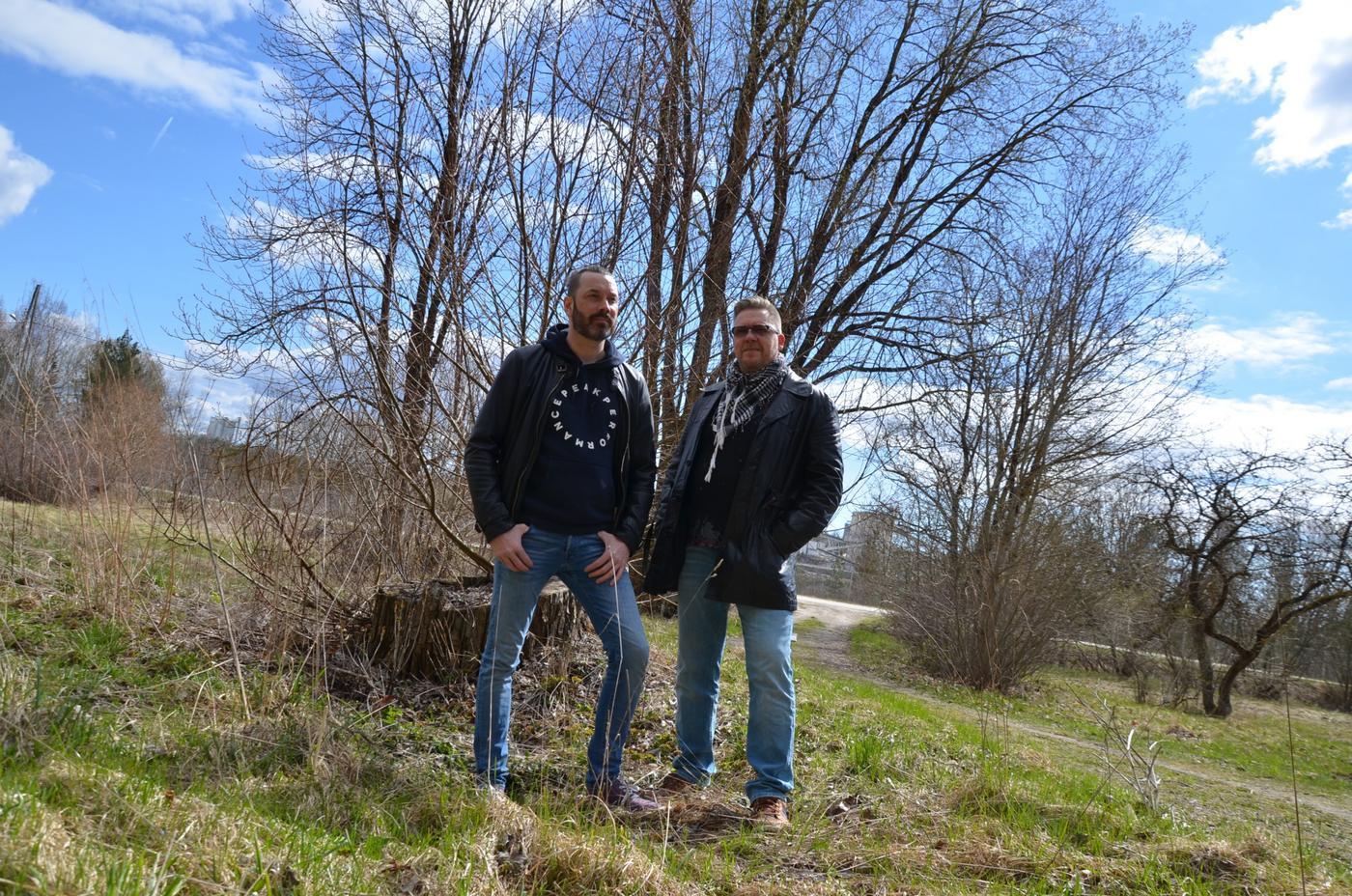 två män poserar framför ett träd