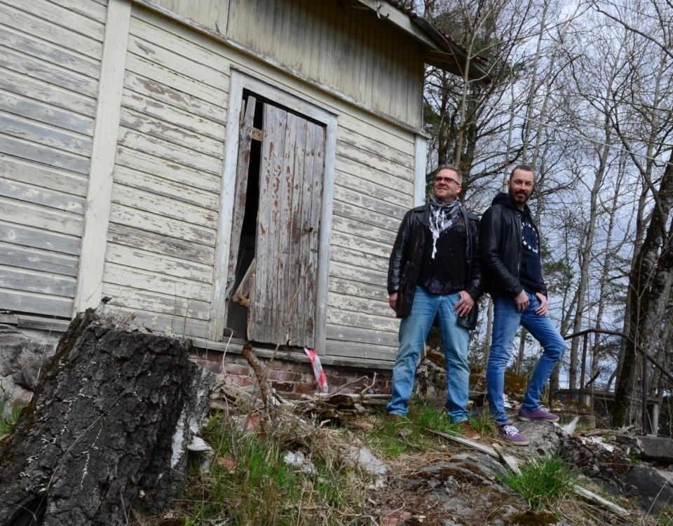 två män poserar framför ett fallfärdigt hus