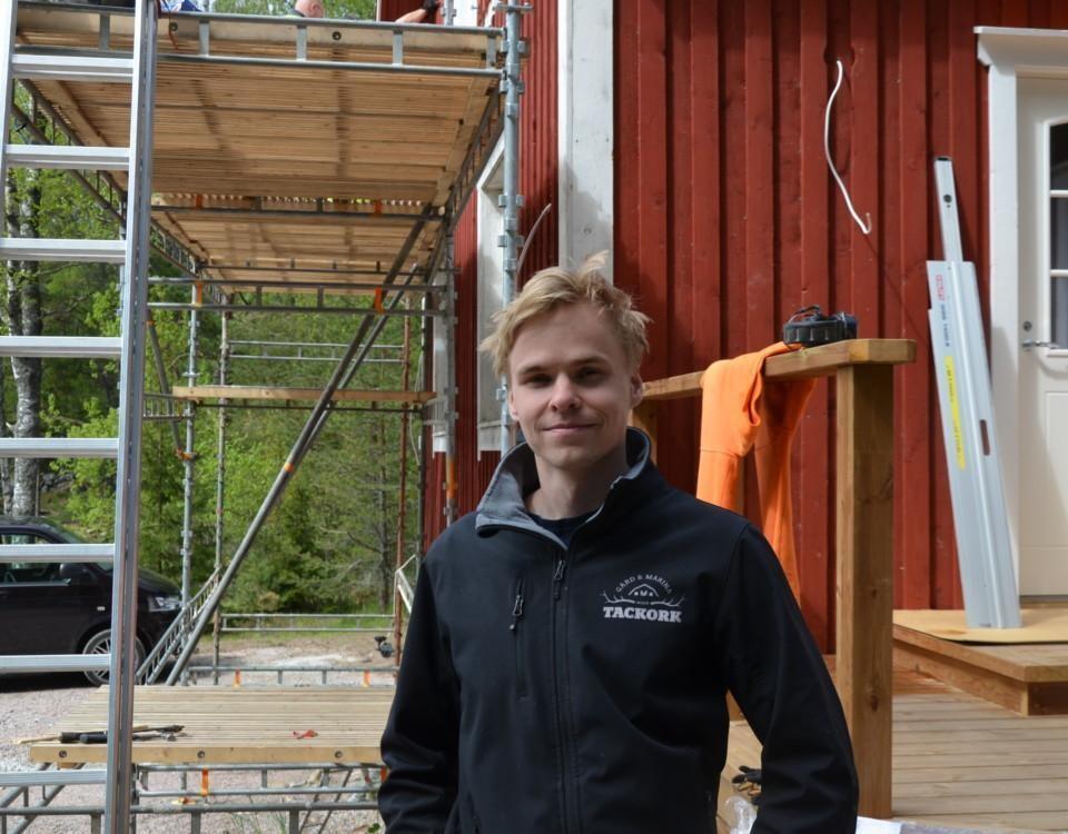 en man står framför ett hus med byggställningar