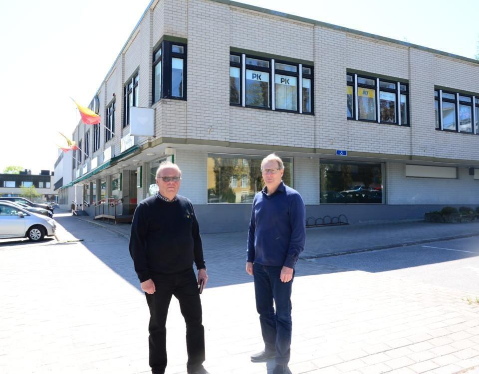 två män står framför ett affärshus i tegel