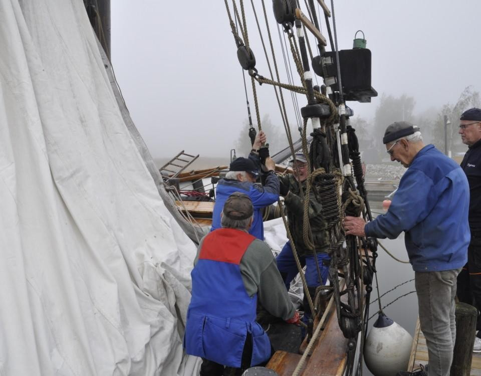 Fem män hissar en segelskutas segel