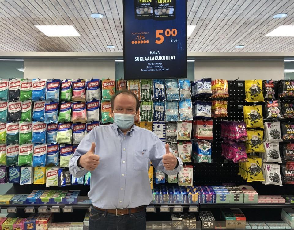 köpman står med munskydd framför godishylla