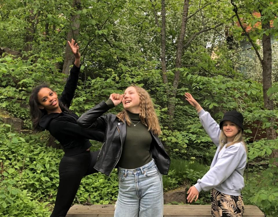 tre flickor står och sjunger