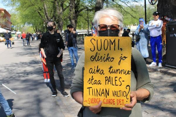 Kvinna som håller upp en skylt med uppmaningen att Finland ska erkänna palestina som en självständig stat.