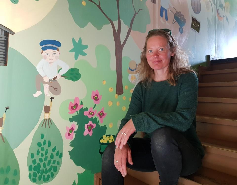 Dam sitter i en trappa med väggmålningar