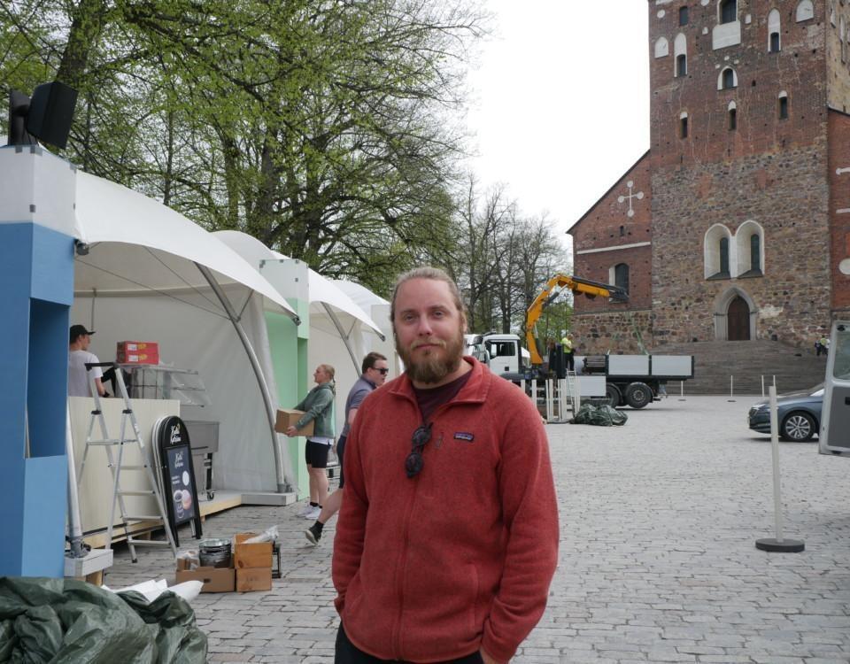 En man står framför Domkyrkan, i bakgrunden syns folk som bär lådor och monterar upp tält.