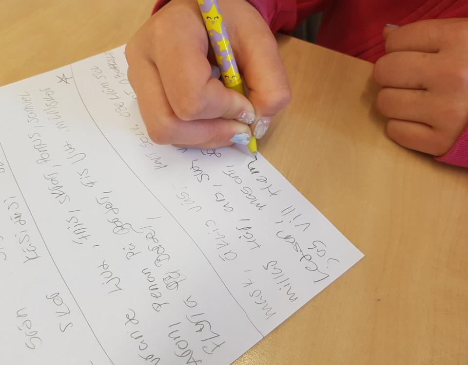 Hand som skriver på papper fyllt med text