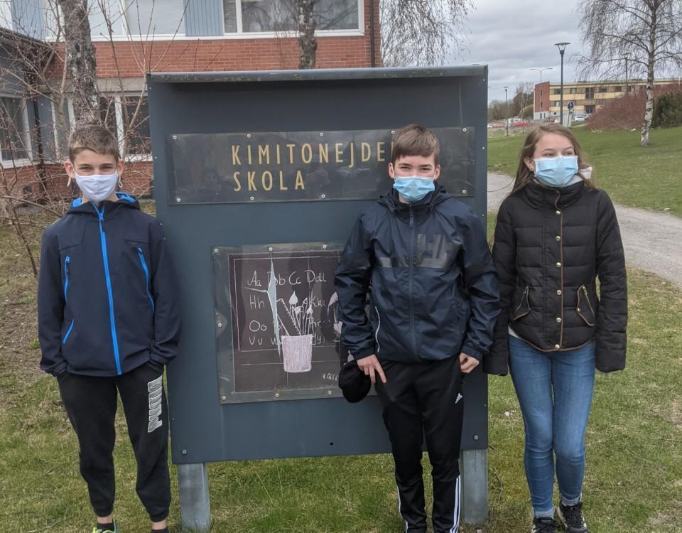 Tre ungdomar utanför en skola.