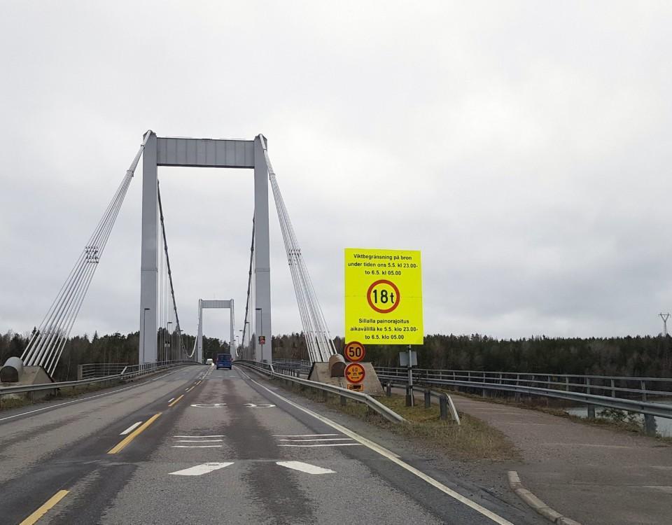 en bro med en stor, gul varningsskylt