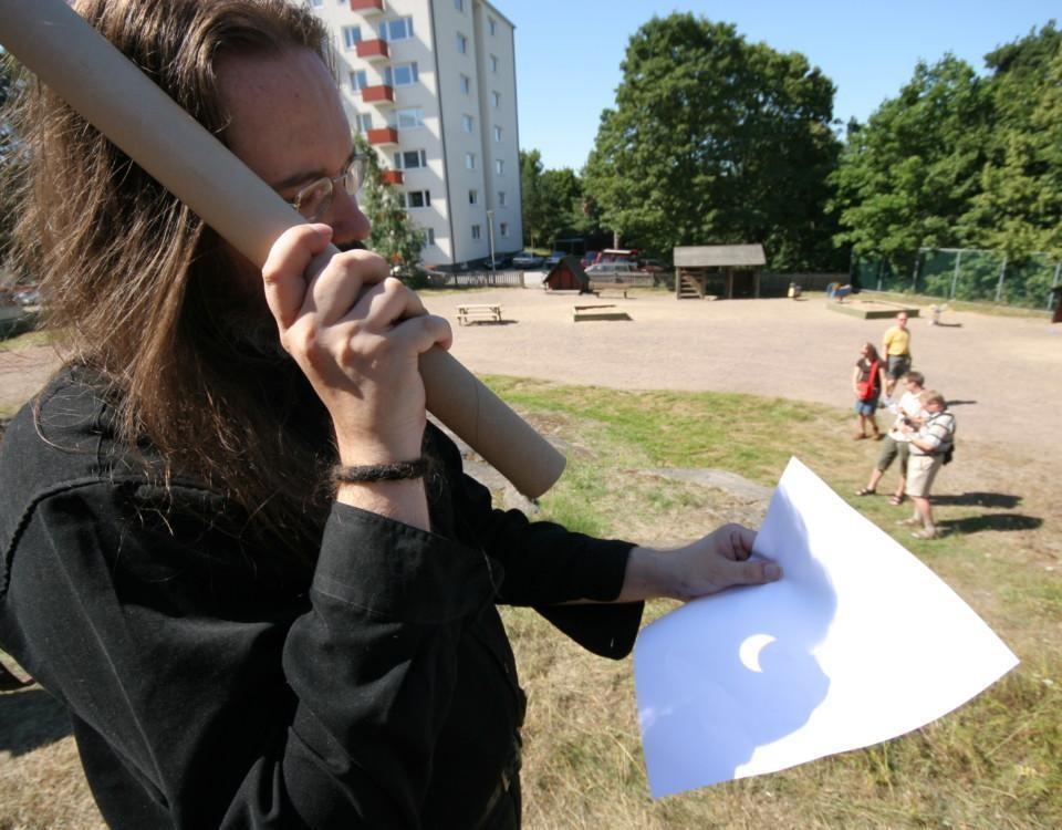 man som håller i ett långt kartongrör mot ett vitt papper.