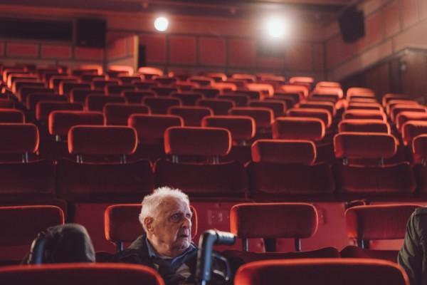 en gammal man sitter ensam i en stor biosalong