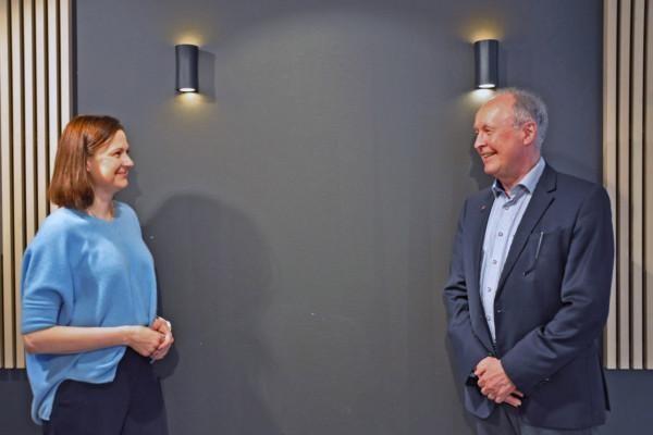Kvinna och man står vid vägg