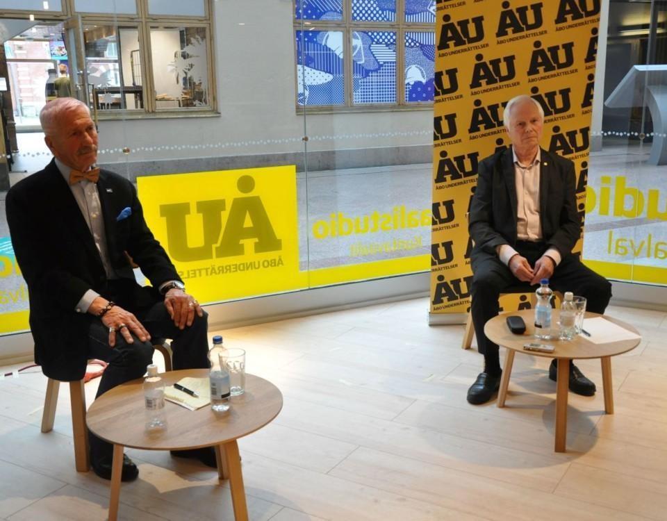 Två män sitter på varsin stol i studio