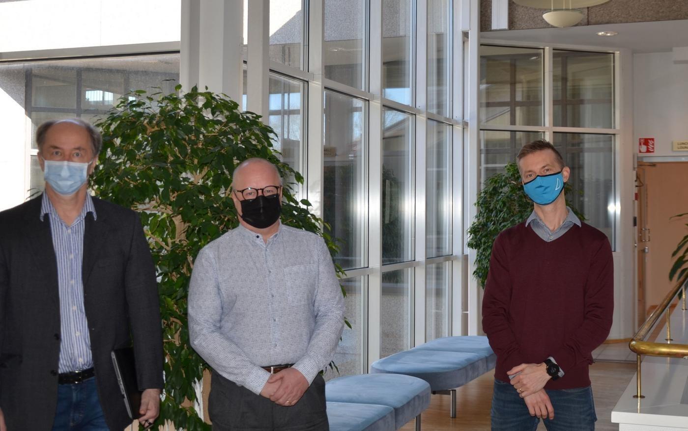 tre män med munskydd i en lobby