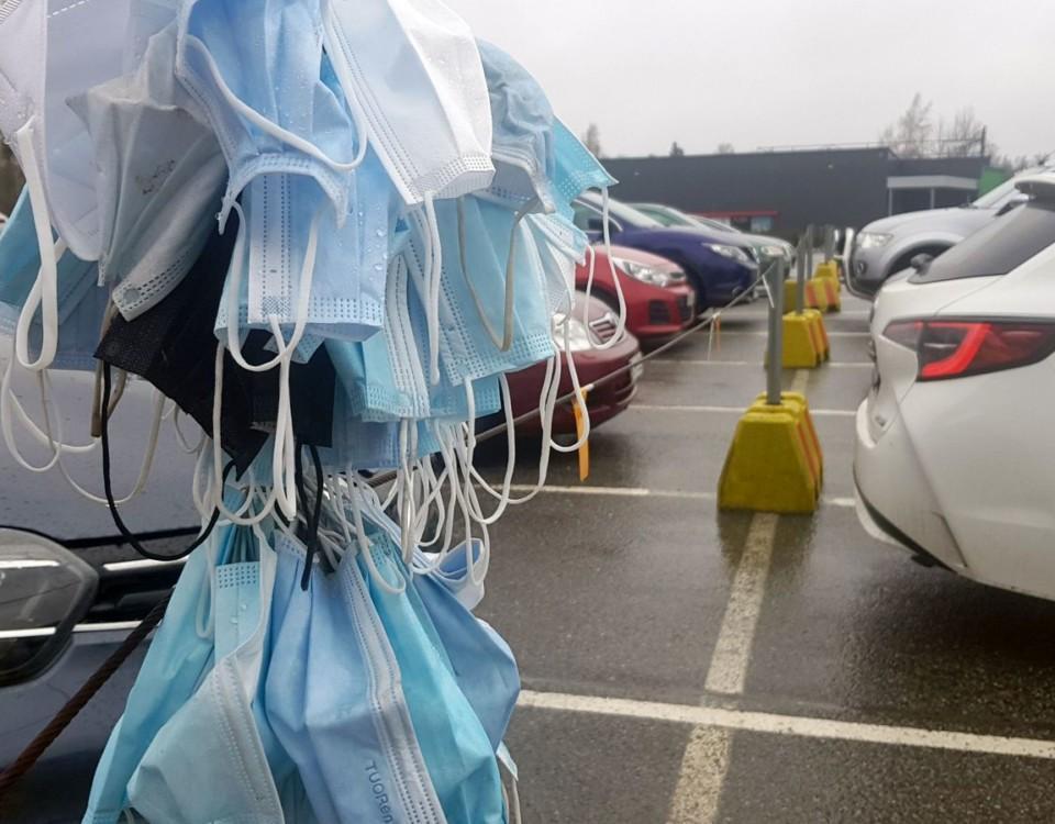 Många munskydd hänger på stolpe på en parkeringsplats