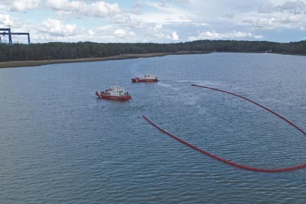 Två oljebekämpningsbåtar och en oljebom