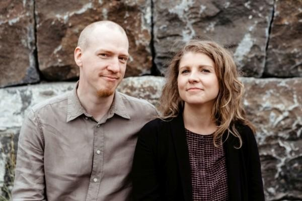 Man och kvinna framför stenmur