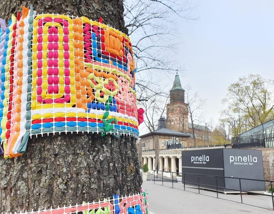 ett stickat och färggrannt konstverk klär ett träd i stan