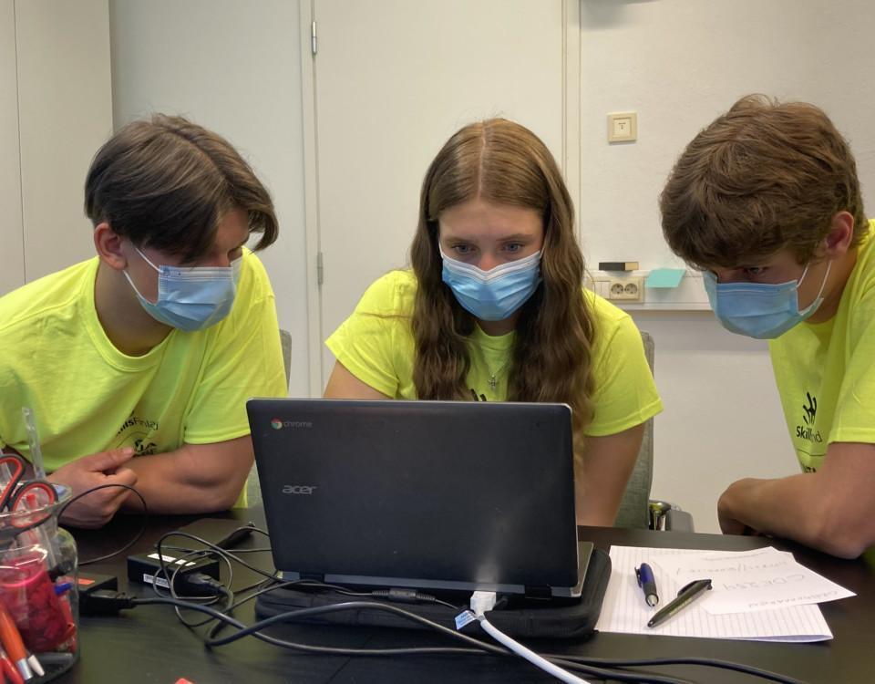 tre skolelever med munskydd framför en bärbar dator