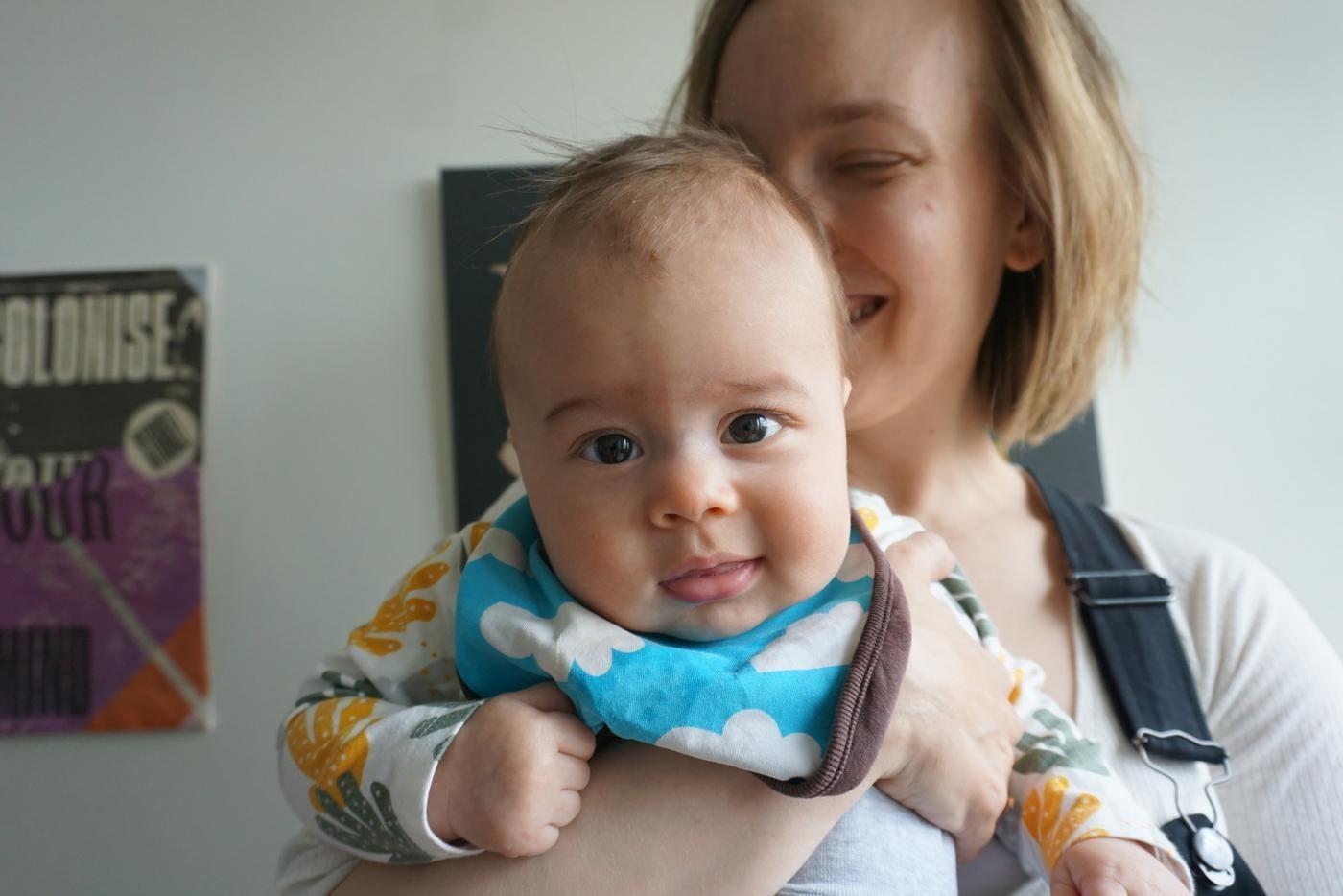 en baby tittar finurligt in i kameran, kvinnan som håller i babyn skrattar