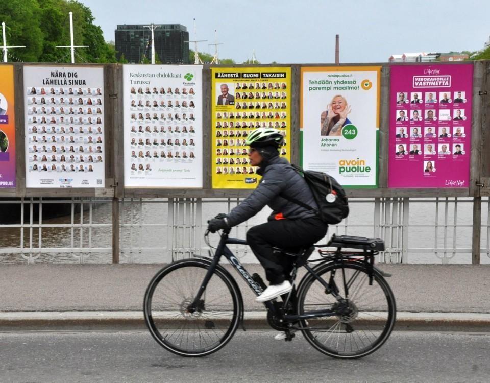Cyklist passerar valplakat