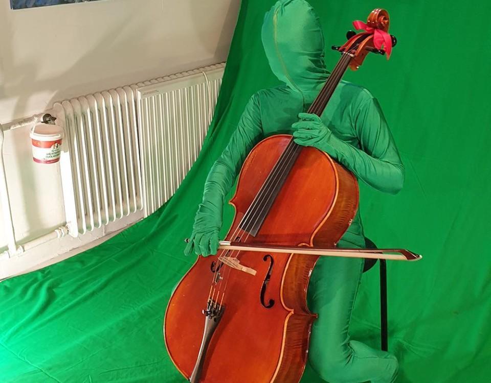 grönklädd figur spelar cello