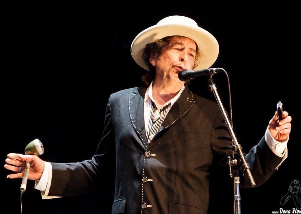 en man med hatt står på en scen och sjunger i en mikrofon mot en mörk bakgrund