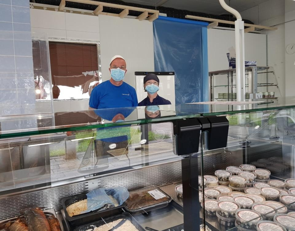 Man och kvinna bakom disken i fiskaffär
