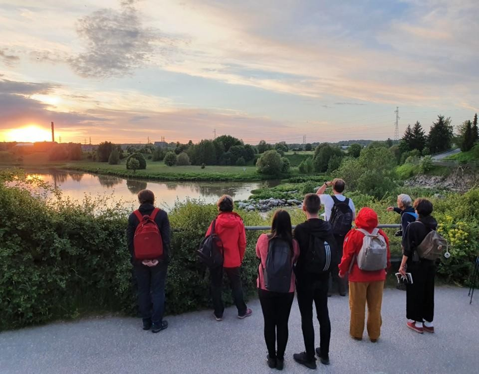 En grupp människor som titter ut över Aura å i solnedgången.