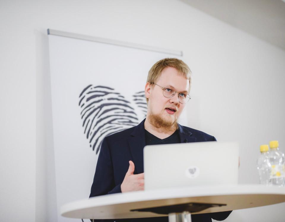 en man med glasögon står bakom en datorskärm och pratar