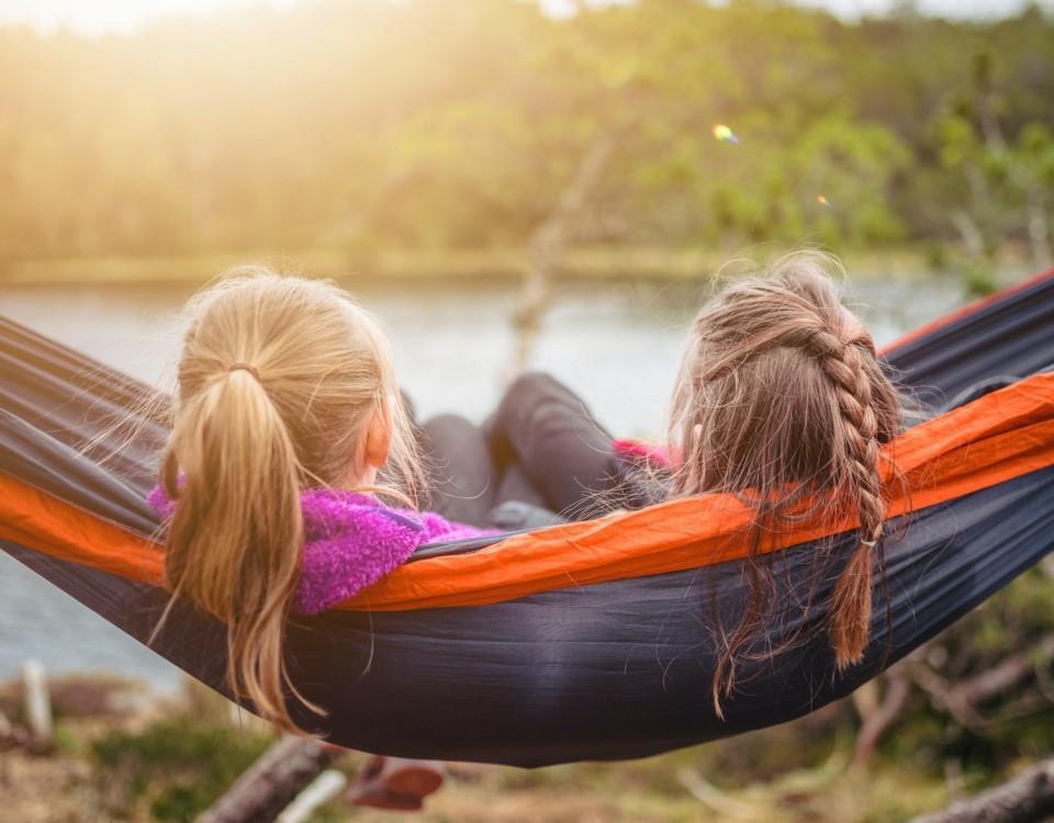 två barn i en hängmatta tittar utåt mot en sjö