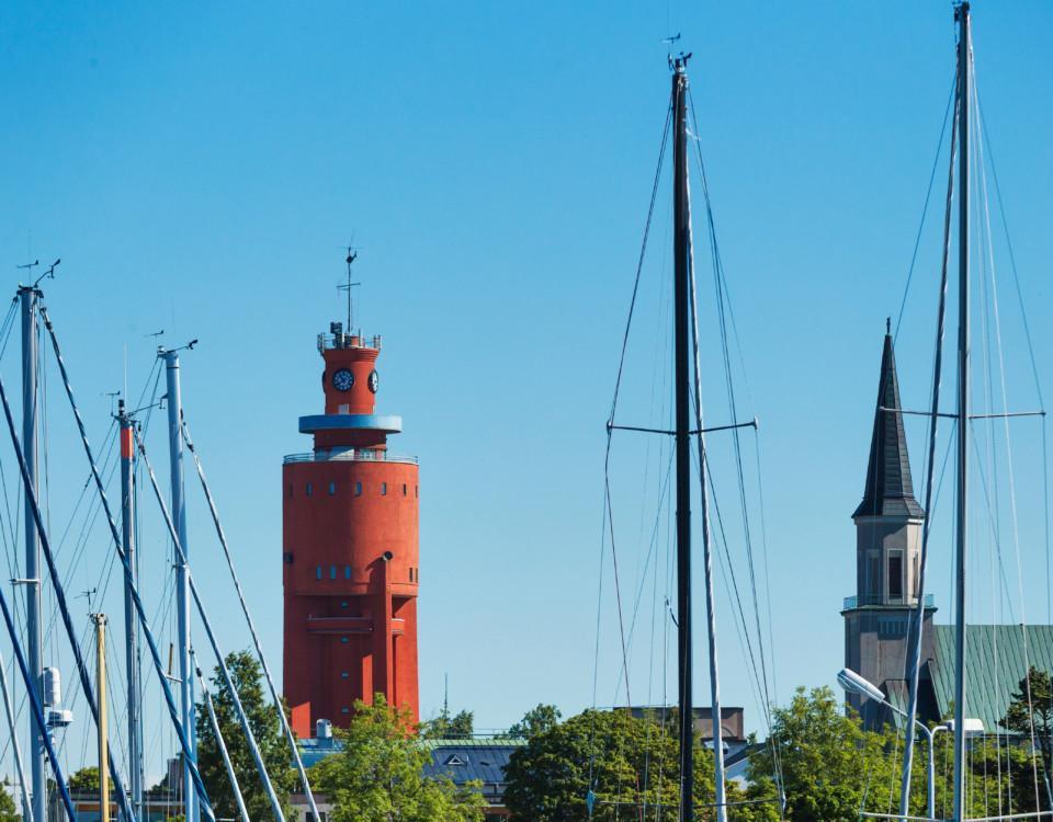 Vy över ett rött torn och segelbåtsmaster.