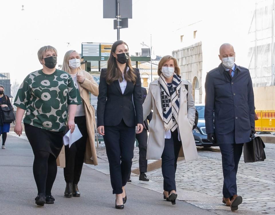 Tre kvinnor och en man går på trottoar