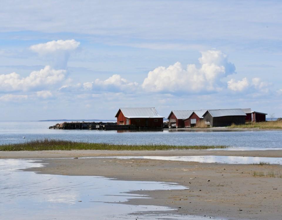 en strand, blå himmel med några moln, röda båthus i bakgrunden