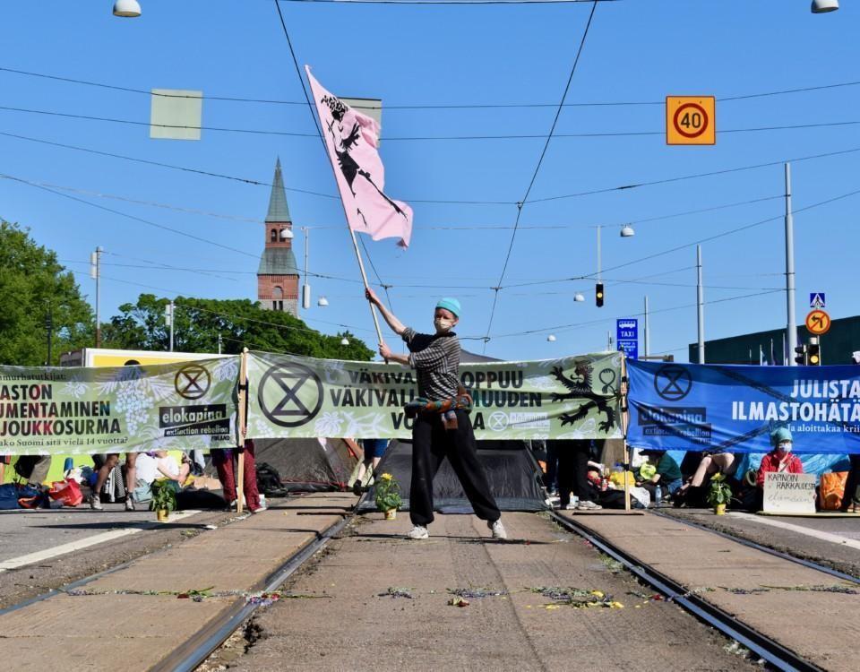 en person står mitt på gatan med en flagga under en demonsration