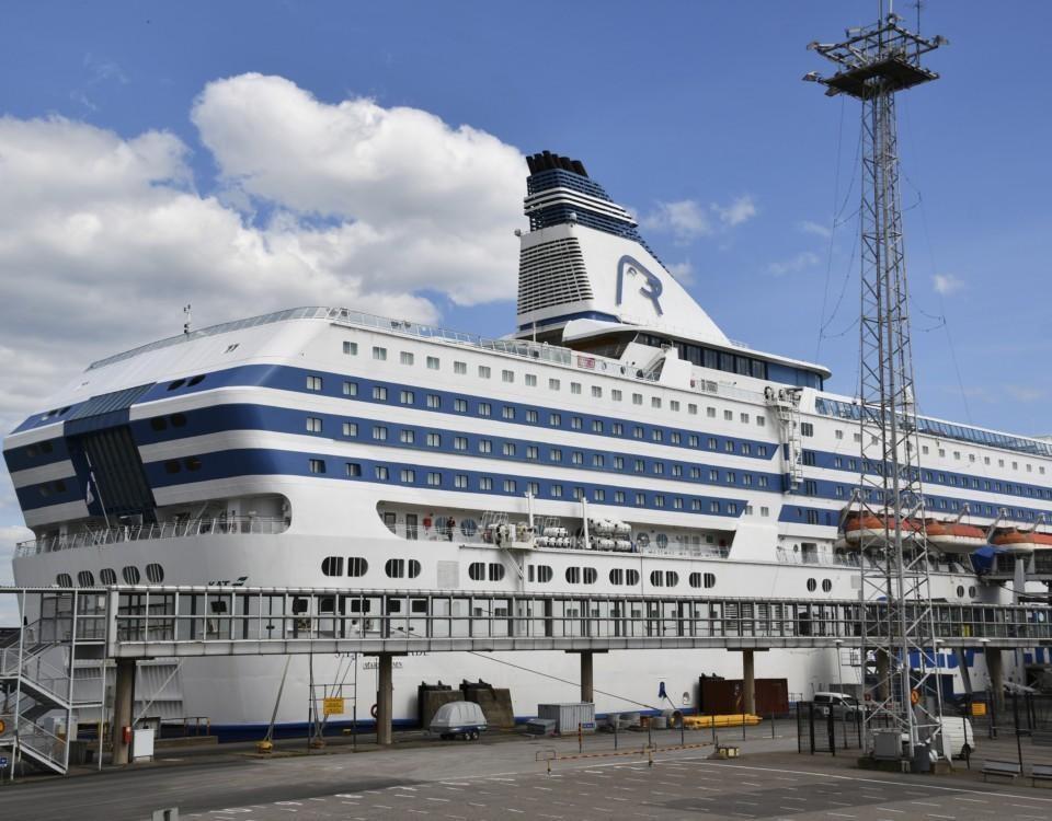 ett stort passagerarfartyg står parkerat vid en kaj