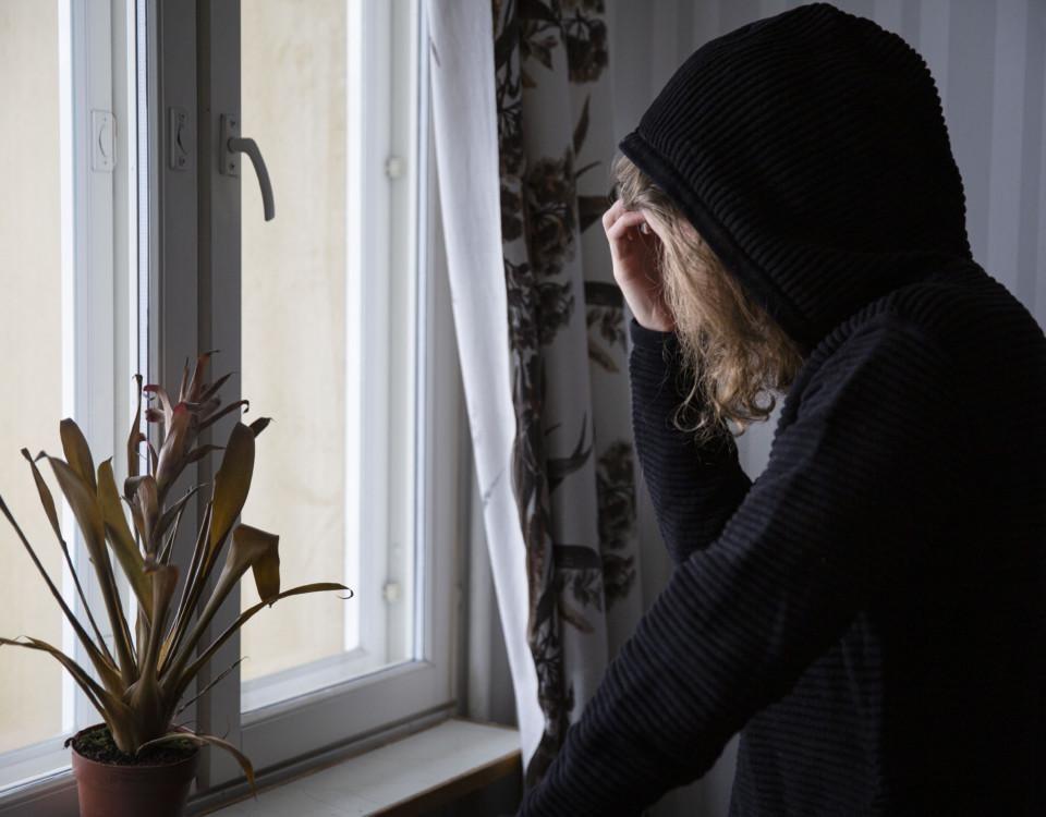 ung person med huva på står vid ett fönster