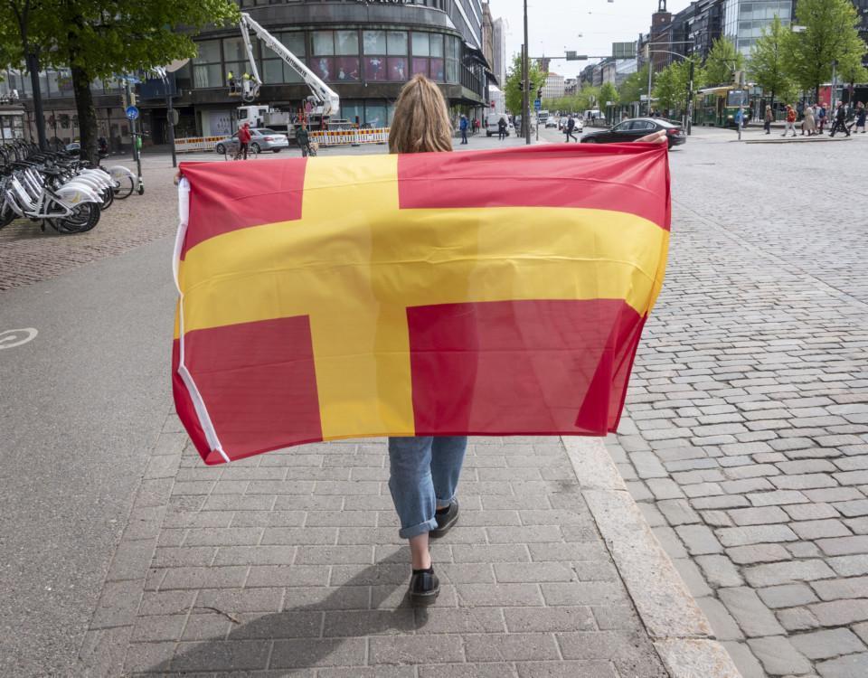 En person håller i en röd flagga med ett gult kors.