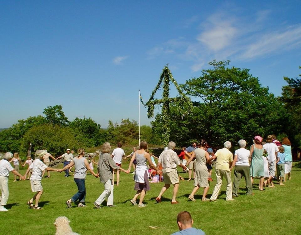 Folk dansar kring en midsommarstång i soligt väder.