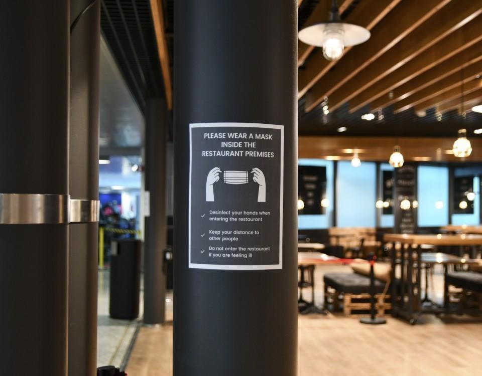 En skylt i en restaurang som visar att man ska ha munskydd på sig.