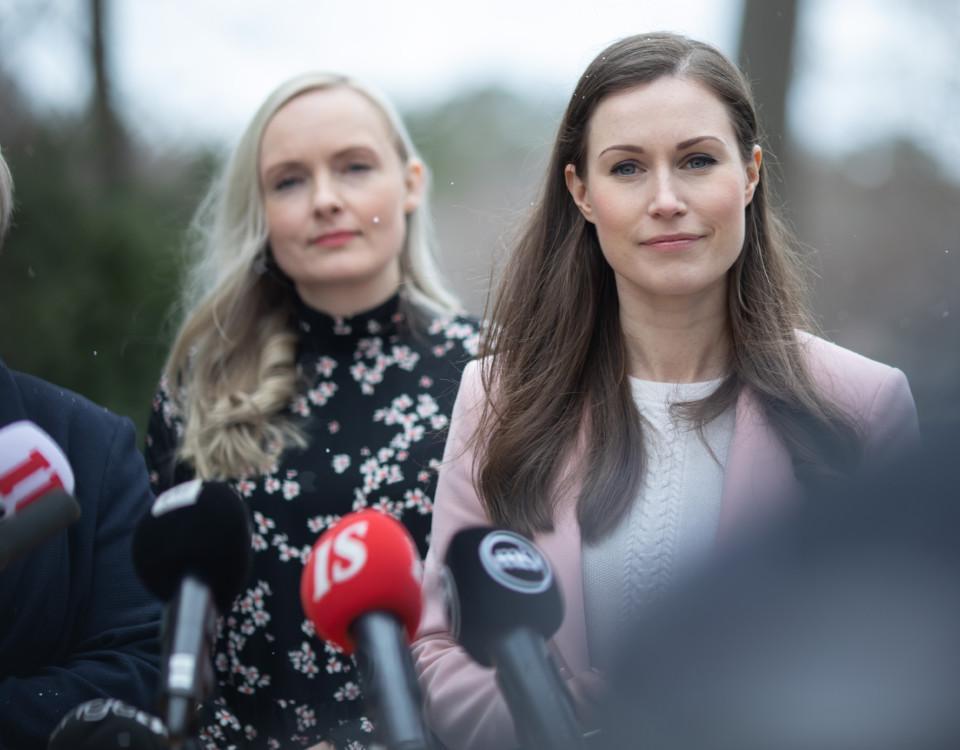 Två kvinnor (Sanna Marin längst fram) står utomhus framför mikrofoner.