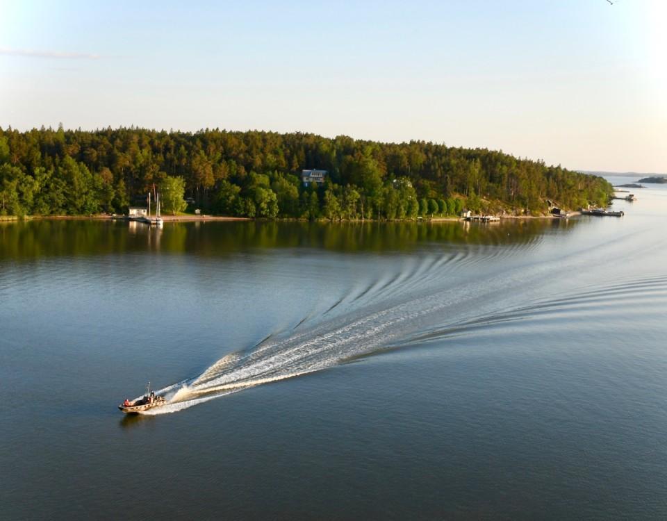 En motorbåt som kör över ett spegelblankt hav.